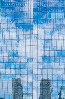 Cielo e nuvole si riflettono in una moderna facciata in vetro dell'edificio