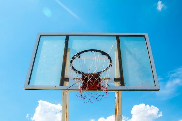 Cielo esterno all'aperto blu del bordo dell'anello del cerchio della rete da pallacanestro all'aperto del campo da pallacanestro.
