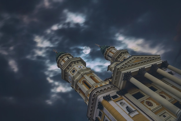 Cielo notturno della chiesa della cattedrale del cattolico greco con la luna e le nuvole nella città ucraina di užhorod