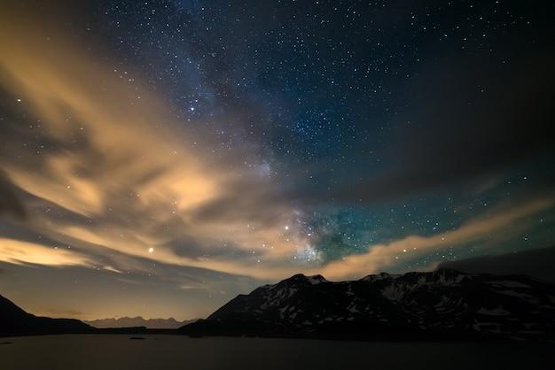 Cielo notturno di astro, stelle della galassia della via lattea sulle alpi, cielo tempestoso, nuvole di movimento, catena montuosa innevata e lago