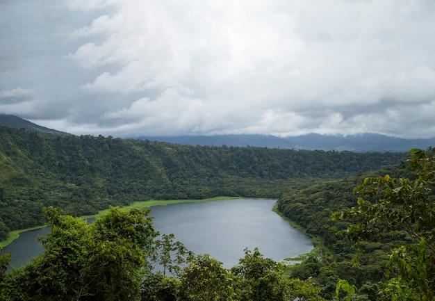 Cielo nuvoloso sopra la bella foresta pluviale e il lago