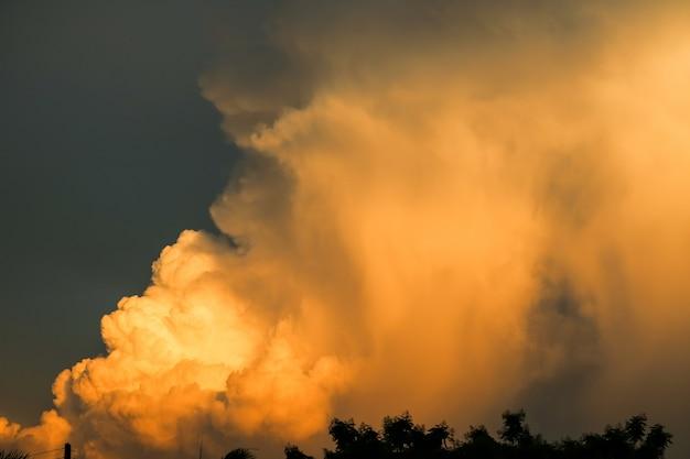 Cielo scuro arancio gigante della nuvola di tramonto del mucchio enorme