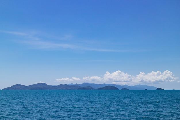 Cielo sereno con un'enorme nuvola sopra le isole e le montagne sul mare
