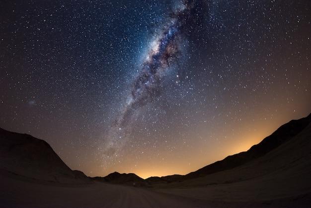 Cielo stellato e arco della via lattea, con dettagli del suo nucleo colorato, straordinariamente luminoso, catturato dal deserto del namib in namibia, in africa. la piccola nuvola di magellano sul lato sinistro.