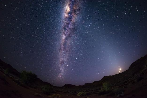 Cielo stellato e arco della via lattea con la luna nel deserto del namib in namibia, africa