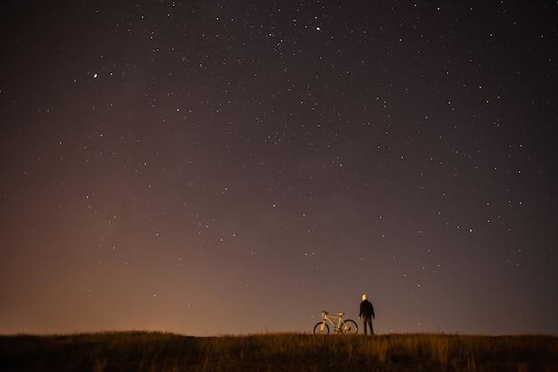 Cielo stellato, fotografia notturna, astrofotografia, la sagoma di un uomo, un uomo in piedi accanto a una mountain bike sullo sfondo di un cielo stellato, la bicicletta bianca