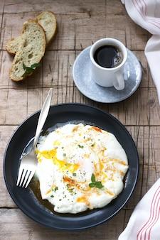 Cilbir, uovo in camicia allo yogurt con burro speziato ed erbe aromatiche, servito con pane e una tazza di caffè.