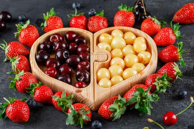 Ciliege con fragole, mirtilli in un piatto di legno sulla superficie grigia, vista di alto angolo.