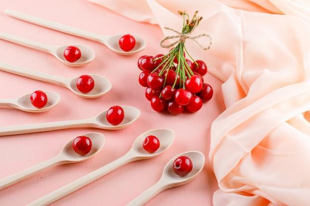 Ciliege in cucchiai di legno sullo spazio del tessuto e di rosa, vista dell'angolo alto.