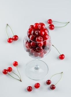 Ciliege in una vista dell'angolo alto di vetro di vino su un bianco
