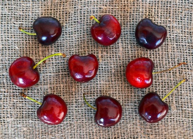 Ciliege organiche mature fresche su un panno della tela da imballaggio. priorità bassa delle bacche della ciliegia.