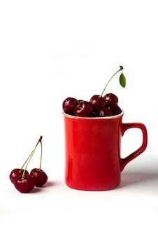 Ciliege rosse in una tazza isolata
