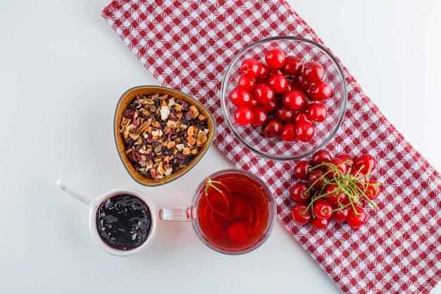 Ciliegia con tè, marmellata, erbe secche in una ciotola su bianco e asciugamano da cucina, piatto laici.