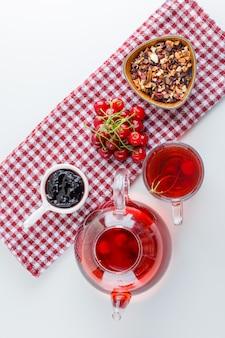 Ciliegia con tè, marmellata, erbe secche su bianco e asciugamano da cucina, vista dall'alto.