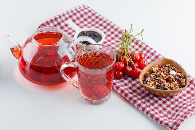 Ciliegia con tè, marmellata, erbe secche vista dall'alto su bianco e asciugamano da cucina