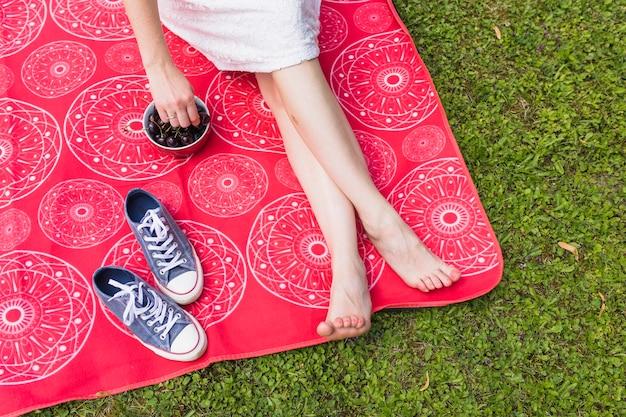 Ciliegia della stretta della donna a disposizione sulla coperta rossa sopra l'erba verde