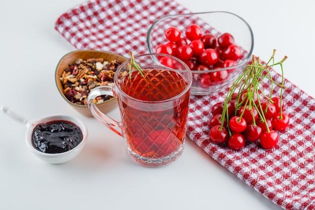 Ciliegia in una ciotola con tè, marmellata, erbe secche alto angolo vista su bianco e asciugamano da cucina
