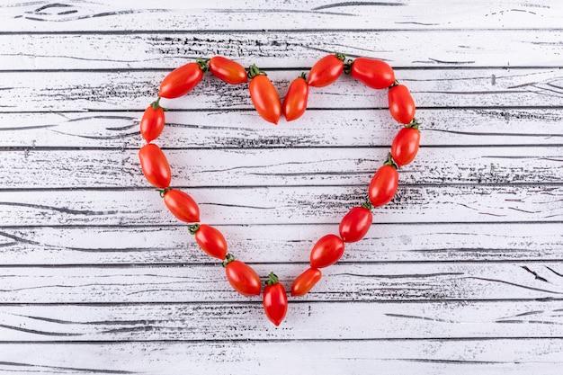 Ciliegia rossa fresca come forma del cuore sulla superficie di legno bianca