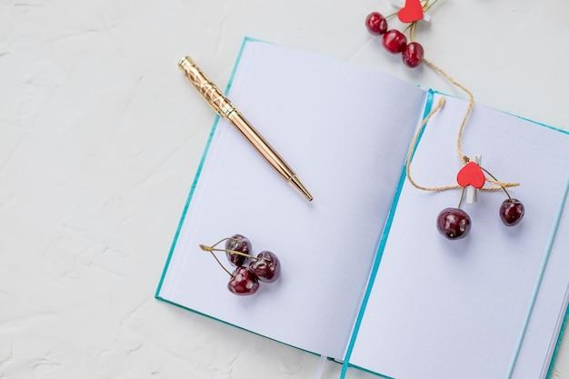 Ciliegie dolci, cuore rosso e taccuino con penna dorata.