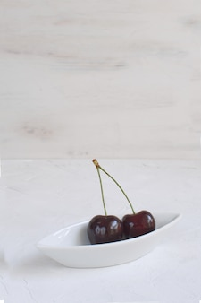 Ciliegie fresche in ciotola di porcellana bianca perdita di peso alimentazione sana frutta e bacche estive raccolta frutta biologica