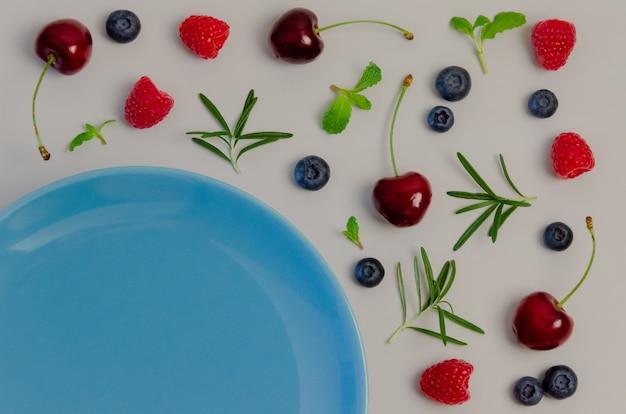 Ciliegie fresche, mirtilli, lamponi, menta e foglia di rosmarino sulla vista dall'alto con il blu.