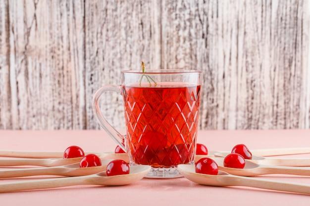 Ciliegie in cucchiai con vista laterale del tè sul tavolo di legno e rosa