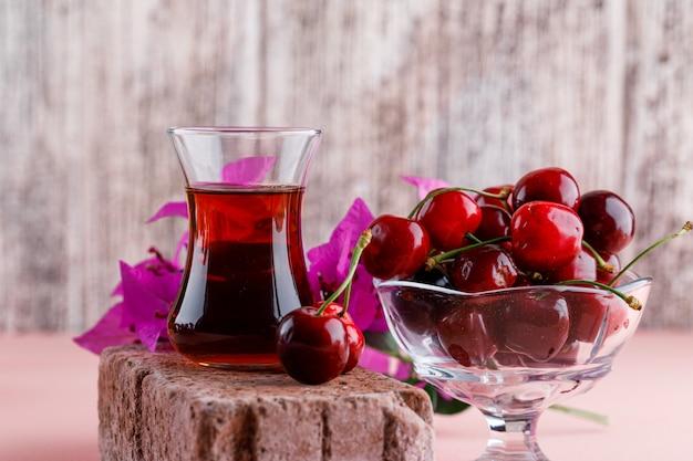 Ciliegie in un vaso con fiori, bicchiere di tè sulla vista laterale di mattoni su superficie rosa e sgangherata