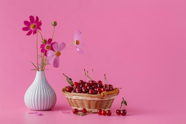 Ciliegie nel cestino su uno sfondo rosa con foglie e fiori