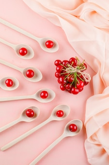 Ciliegie nella vista superiore dei cucchiai di legno sullo spazio del tessuto e di rosa