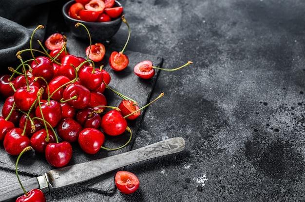 Ciliegie rosse sul tagliere nero