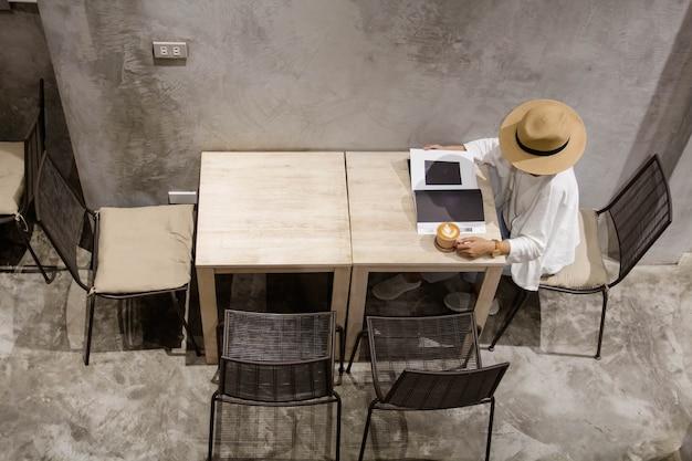 Cima del libro di lettura dell'adolescente e bere caffè al caffè