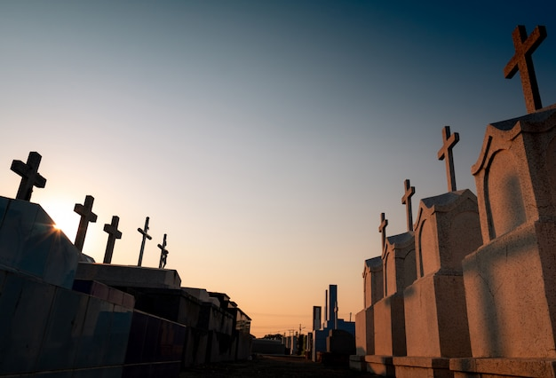 Cimitero o cimitero di sera con il cielo al tramonto. lapide e croce tombale cimitero. riposa in pace. concetto funebre. tristezza, lamento e morte passerella tra il cimitero.