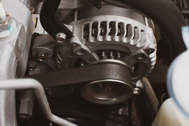 Cinghia di distribuzione di vecchio alternatore nel sistema del motore dell'automobile, concetto della parte automobilistica.