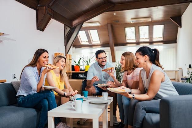 Cinque amici si divertono a mangiare la pizza a casa.