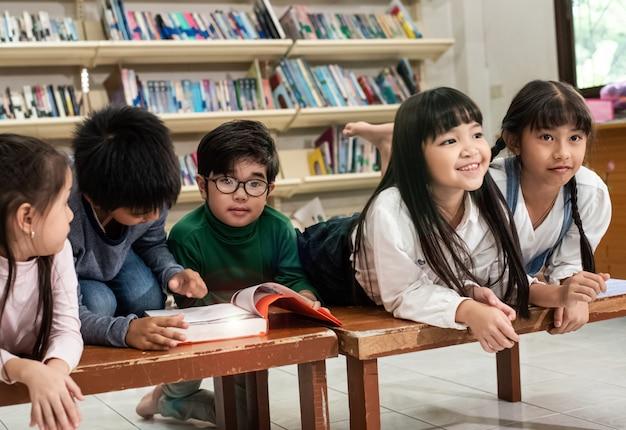 Cinque bambini sdraiati sulla scrivania di legno, parlando e leggendo un libro, facendo attività insieme, a scuola, effetto riflesso lente, luce sfocata intorno