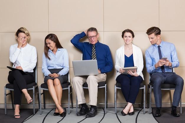 Cinque candidati contenuti seduto in sala di attesa