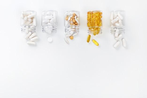Cinque confezioni con varie pillole bianche e dorate su uno sfondo bianco. concetto di salute. vista dall'alto con spazio di copia.