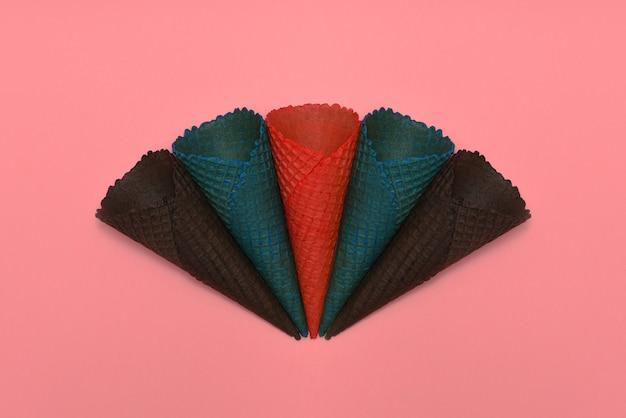 Cinque coni gelato multicolore wafer si trovano su uno sfondo rosa