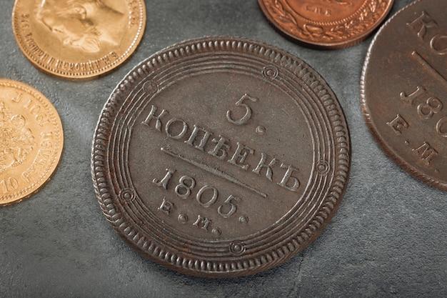 Cinque copechi della russia zarista. numismatica. vecchie monete da collezione in argento, oro e rame su un tavolo di legno. vista dall'alto.