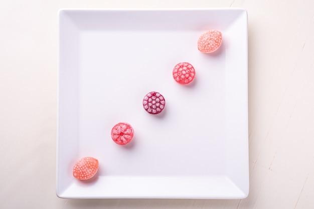 Cinque dolci dei bastoncini di zucchero nella forma di bacche succose sul piatto bianco su fondo bianco isolato, vista superiore