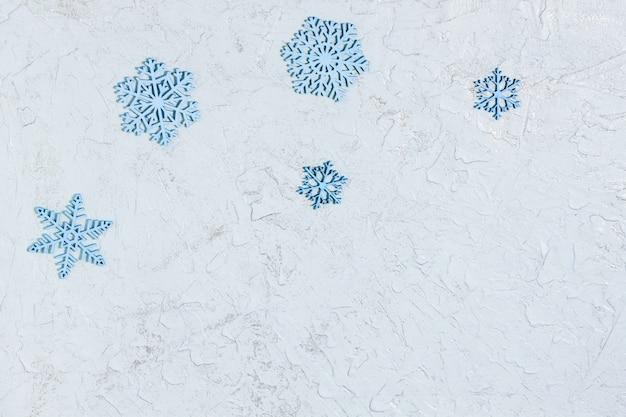 Cinque fiocchi di neve in legno blu sulla superficie glitterata
