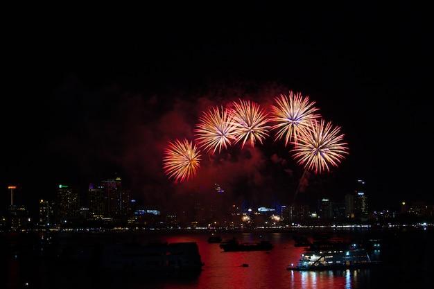 Cinque fuochi d'artificio sulla spiaggia e il colore riflesso sulla superficie dell'acqua