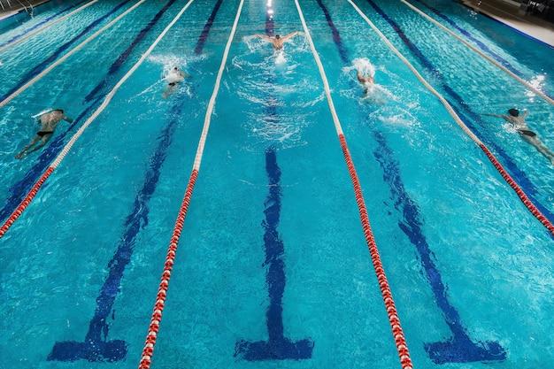 Cinque nuotatori che corrono uno contro l'altro in una piscina