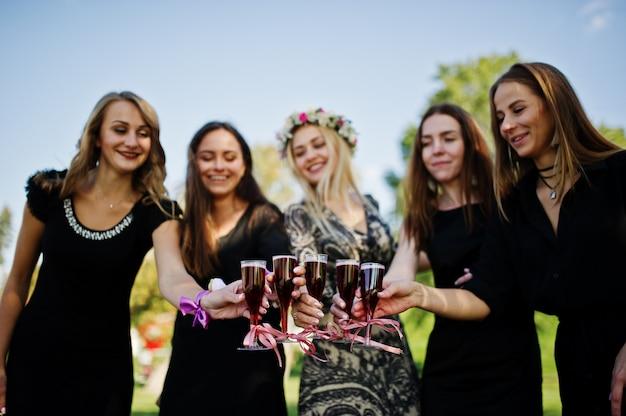 Cinque ragazze indossano il nero con palloncini bevendo champagne rosso al addio al nubilato.