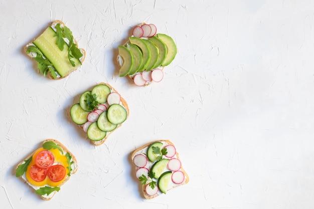 Cinque sandwich vegani o vegetariani su uno sfondo bianco, spazio per il testo