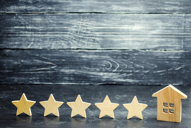 Cinque stelle e una casa di legno su uno sfondo grigio cemento. il concetto del miglior alloggio