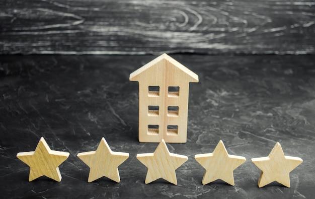 Cinque stelle e una casa di legno su uno sfondo grigio cemento.