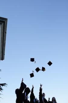Cinque studenti laureati che gettano il cappello in cielo