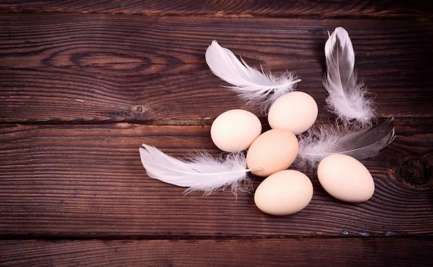 Cinque uova di gallina crude con piume