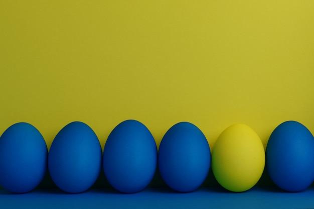 Cinque uova di pasqua dipinte di blu e di uno giallo stanno in fila su un giallo con sfondo blu
